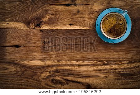 Cup of coffee on dark brown wooden table above view