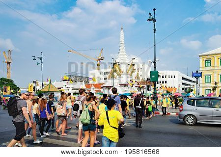 Bangkok, Thailand - December 5, 2015: Street view of historical center of Bangkok, Thailand. People at pedestrian crossing in Sanam Chai Road, City Pillar Shrine Lak Muang on the horizon.
