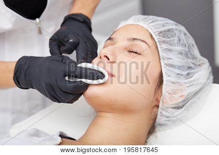 Cosmetologist making permanent makeup on woman's face