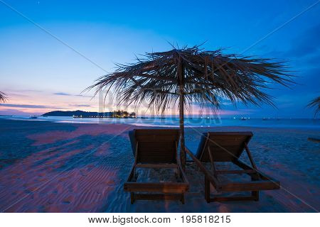 Sunset on the beach deck chairs with an umbrella. Copy space for text