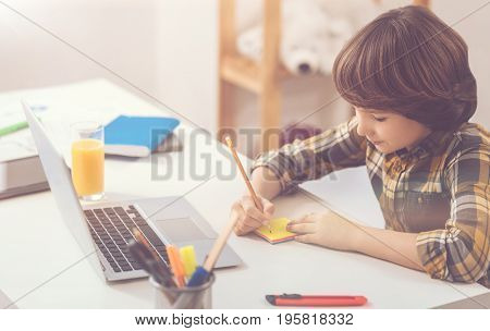 Creative assignment. Serious pleasant diligent boy sitting at the table and holding a pencil while writing on the sticky notes