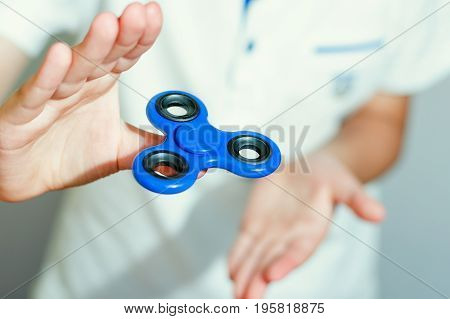 Boy in a white T-shirt is played with a blue spinner