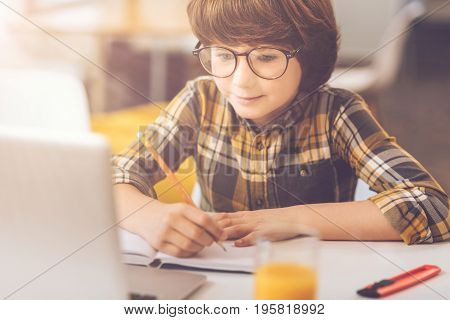 My home task. Cute clever nice boy sitting in front of the laptop and making notes while doing his homework