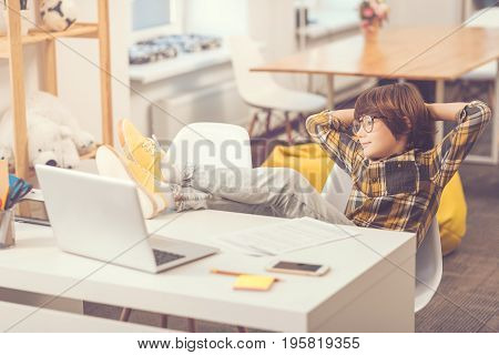 Like a boss. Confident pleasant relaxed boy sitting in the chair and putting his legs on the table while imagining being a boss