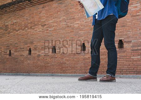 Young Traveler Reading Map. Asian Man Wearing Blue Shirt And Jeans Standing Near Old Orange Brick Wa