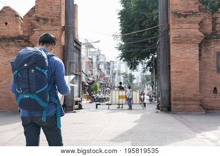 CHIANG MAI, THAILAND - JUNE 29: young asian man wearing blue jacket and jeans reading map while standing near old orange brick wall with backpack at Tapae gate in Chiang Mai Thailand on June 29 2017.