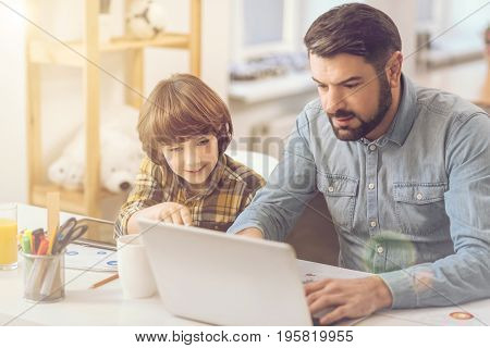 Helping with a home task. Handsome nice caring father sitting at the laptop and typing while helping his son with home task