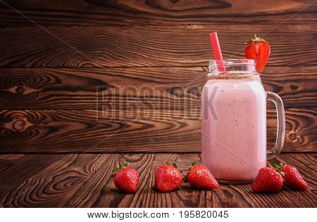 Fresh strawberry yogurt in a mason jar with red straw on a dark brown wooden background. A mason jar with handle and red straw filled with a pink strawberry smoothie and a lot of sweet berries around.
