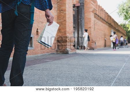 Young Asian Man Wearing Blue Shirt And Jeans With Map And Backpack Standing Near Old Brick Wall