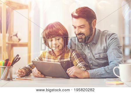 Father and son. Joyful happy handsome man holding a tablet and looking at its screen while spending time with his son