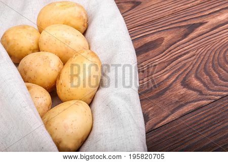 Nutritious organic potatoes. Summer harvest of fresh potatoes on a light grey fabric and on a dark brown wooden table. Organic and uncooked new potatoes. Fresh vegetables.