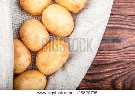 A lot of fresh and organic potatoes on a light gray fabric and on a dark brown wooden background. Close-up of ripe and new potatoes, top view. Young potatoes. New harvest of vegetables from a garden.