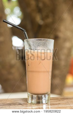 Glass Of Cold Coffee On Wood outside, tree on a background.