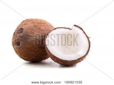 Close-up of healthful coconuts, isolated on a white background. Hawaiian, whole and cut in a half coconuts. Organic ingredients for cooking vegan meals. Nutritious exotic nuts.