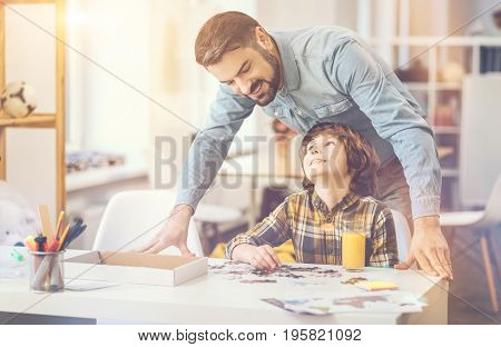 Caring father. Joyful happy positive father standing behind his son and smiling while looking at the jigsaw puzzle picture