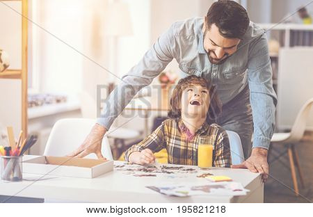 Pleasurable moments. Happy delighted nice father and son doing jigsaw puzzle and laughing while having fun together