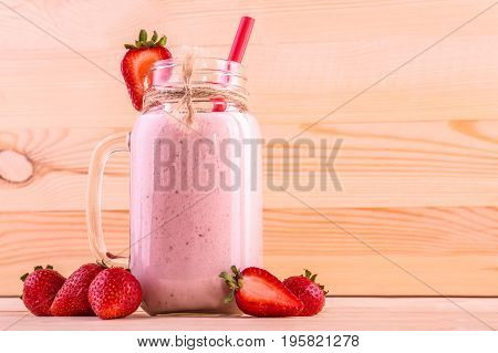 A mason jar filled with a bright red strawberry drink with a red straw and sweet berries around on a light brown background. Tasty and bright pink cocktail. Summer drink from strawberries and milk.