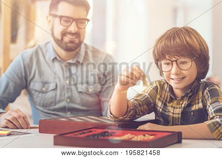 Chess game. Delighted intelligent positive boy holding a chess piece and looking at it while sitting with his father