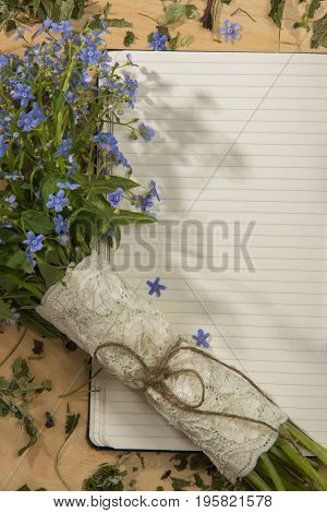Spring bouquet of forget-me colors in the morning sun on the notebook on the wooden table