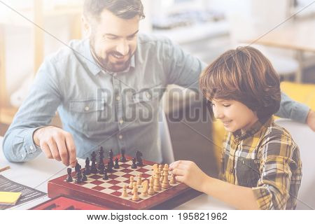 I go first. Cute positive delighted boy taking a chess piece and doing the first chess move while playing with his father