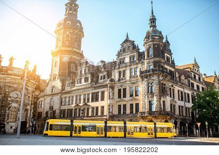 View on the old castle with Hausmannsturm tower and yellow tram in Dresden city during the sunrise in Germany