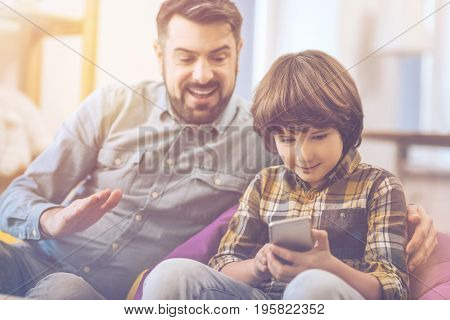 Friendly atmosphere. Cute joyful delighted boy holding his smartphone and using it while sitting next to his father