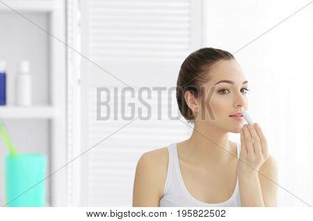 Woman applying hygienic lip balm in light room
