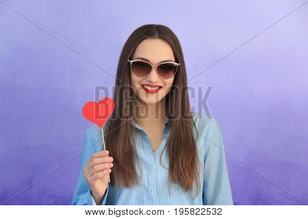 Beautiful young woman with bright lips on color background