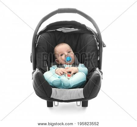 Adorable baby boy with pacifier sitting in car seat on white background