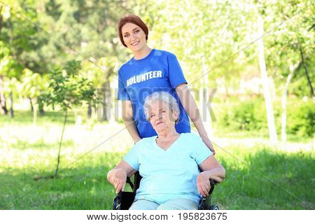 Happy senior woman on wheelchair with young female volunteer outdoors