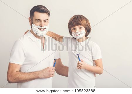 Time for shaving. Positive nice delighted father and son standing together and holding razors while shaving