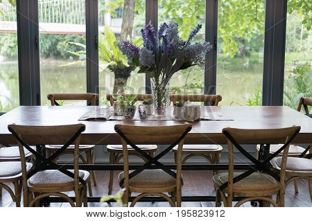 Wood Table And Chair In Dining Room Beside Window With Lake And Garden View. Home Interior