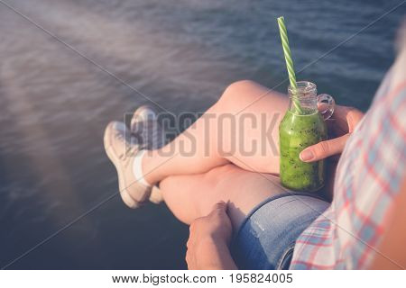Female enjoying the sea view and holding glass bottle of kiwi smoothie outdors. Summer and healthy lifestyle concepts.