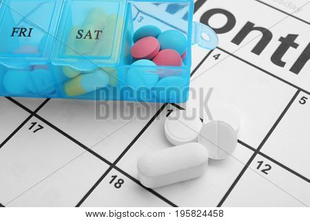 Plastic container with pills on paper calendar, closeup