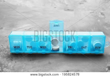 Plastic container with pills on grey textured table