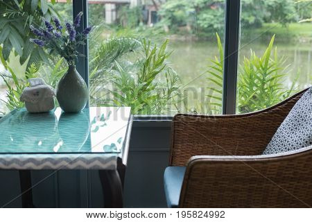 Rattan Chair With Pillow In Living Room In Modern House Beside Window With Garden And Lake View. Hom