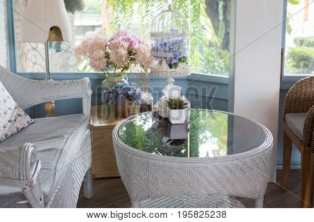 Blue Rattan Sofa With Pillow In Living Room Beside Window With Garden View In Modern House. Home Int