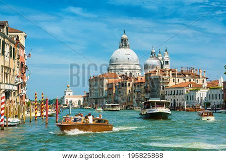 Venice, Italy - May 19, 2017: Water taxis and vaporetto with tourists are sailing along the Grand Canal in Venice. Motor boats are the main transport in Venice. Santa Maria della Salute church in the distance.