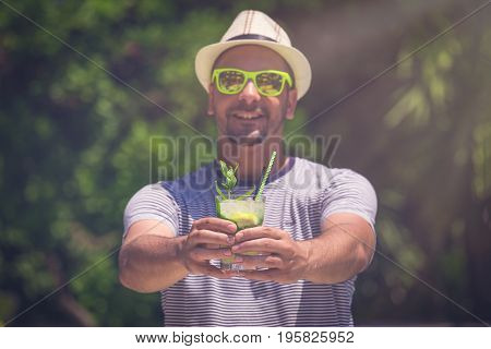 Portrait of mann in hat and sunglasses holding and showing mojito cocktail. Summer vacation and travel concepts.