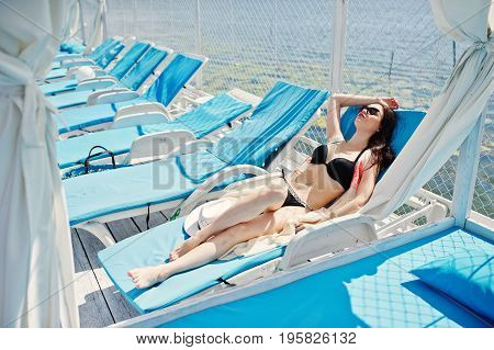 Portrait Of A Beautiful Girl Wearing Black Bikini Swimsuit And Sunglasses Laying On The Lounger By T