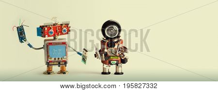 Robotic maintenance repair fix concept. Handyman robots, smiley red head, chip usb flash stick. Mechanic cyborg toy with black helmet, electronic accessories, screwdriver. Copy space, beige background.