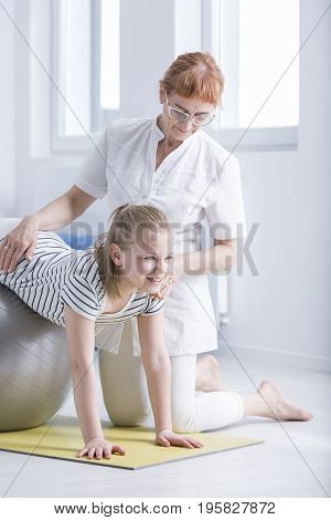 Physiotherapist Supporting Girl With Scoliosis