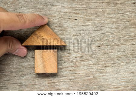 Wooden block puzzle in home shape waits for completion (Concept for family building or dream life)