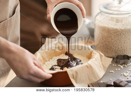 Woman pouring chocolate onto rice dessert in baking dish on table