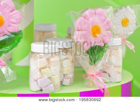Tasty marshmallow in jars and lollipops at candy shop