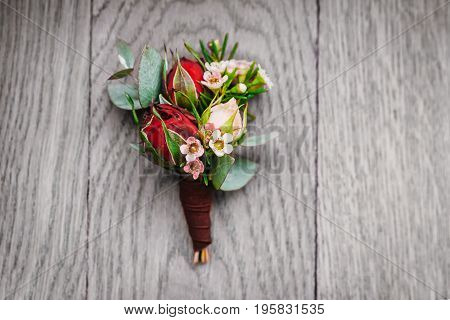Boutonniere groom on a gray wooden background. Close-up. Horisontal