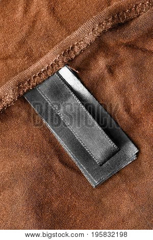 Black clothes label on terracotta cotton as a background