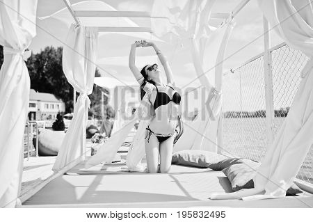 Portrait Of An Amazing Girl In Black Bikini Swimsuit Posing On Her Knees On Lounger By The Lake. Bla