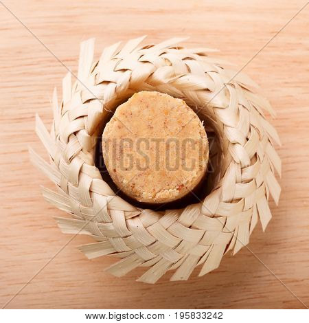 Pacoca - brazilian candy of ground peanut in wicker hat of Festa Junina. Selective focus. Copy space