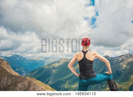 Woman hiker standing on the top of mountain outdoor. Back pose